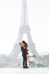 A couple kisses in front of the Eiffel Tower during their engagement session in Paris.