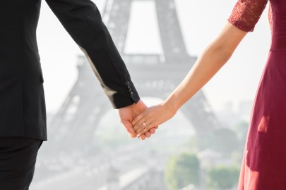 A bride and groom hold hands in front of the Eiffel Tower during an engagement session in Paris.