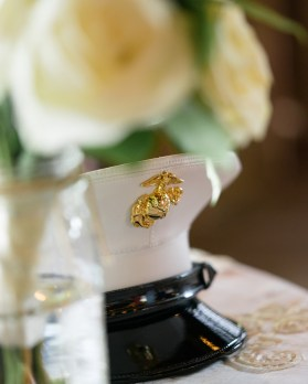 A Marine's cover framed my white roses during a military wedding.