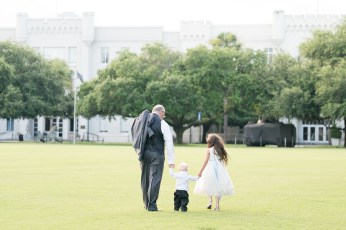 A grandfather walks hand in hand with his grandchild following a wedding at The Citadel.