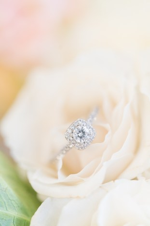 A bride' engagement ring photographed sitting inside a white rose.