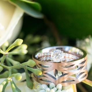 The bride's engagement ring and groom's band set against a backdrop of fresh flowers.
