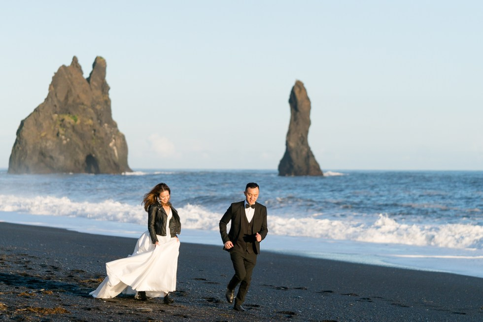 A couple runs along the black sand beach near Vik, Iceland