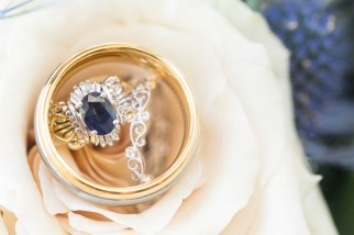 Vintage engagement ring and custom wedding bands photographed against the bride's bouquet of white roses.