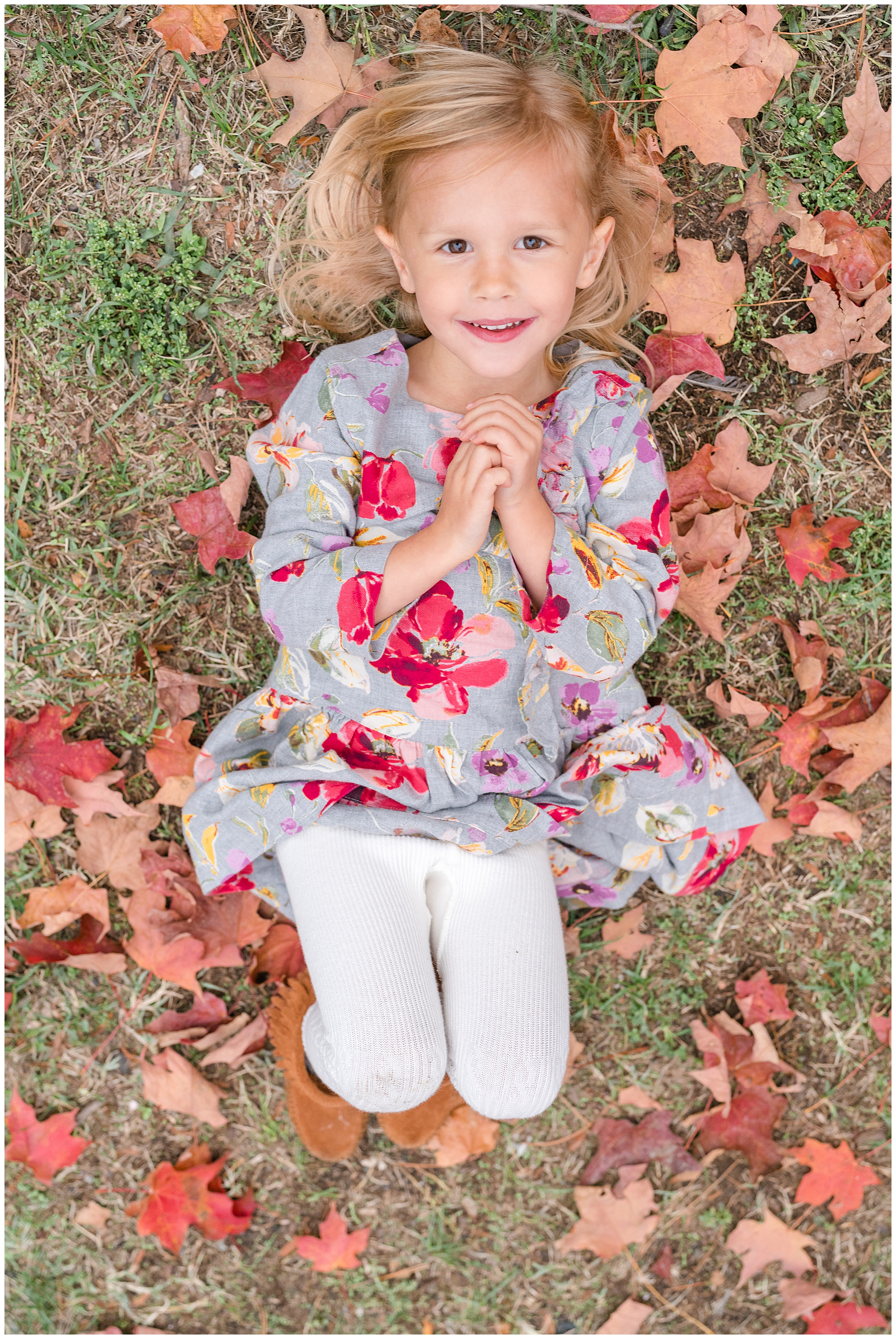 A blonde girl in a gray dress plays in fallen leaves during a fall family session in Alexandria, Virginia.