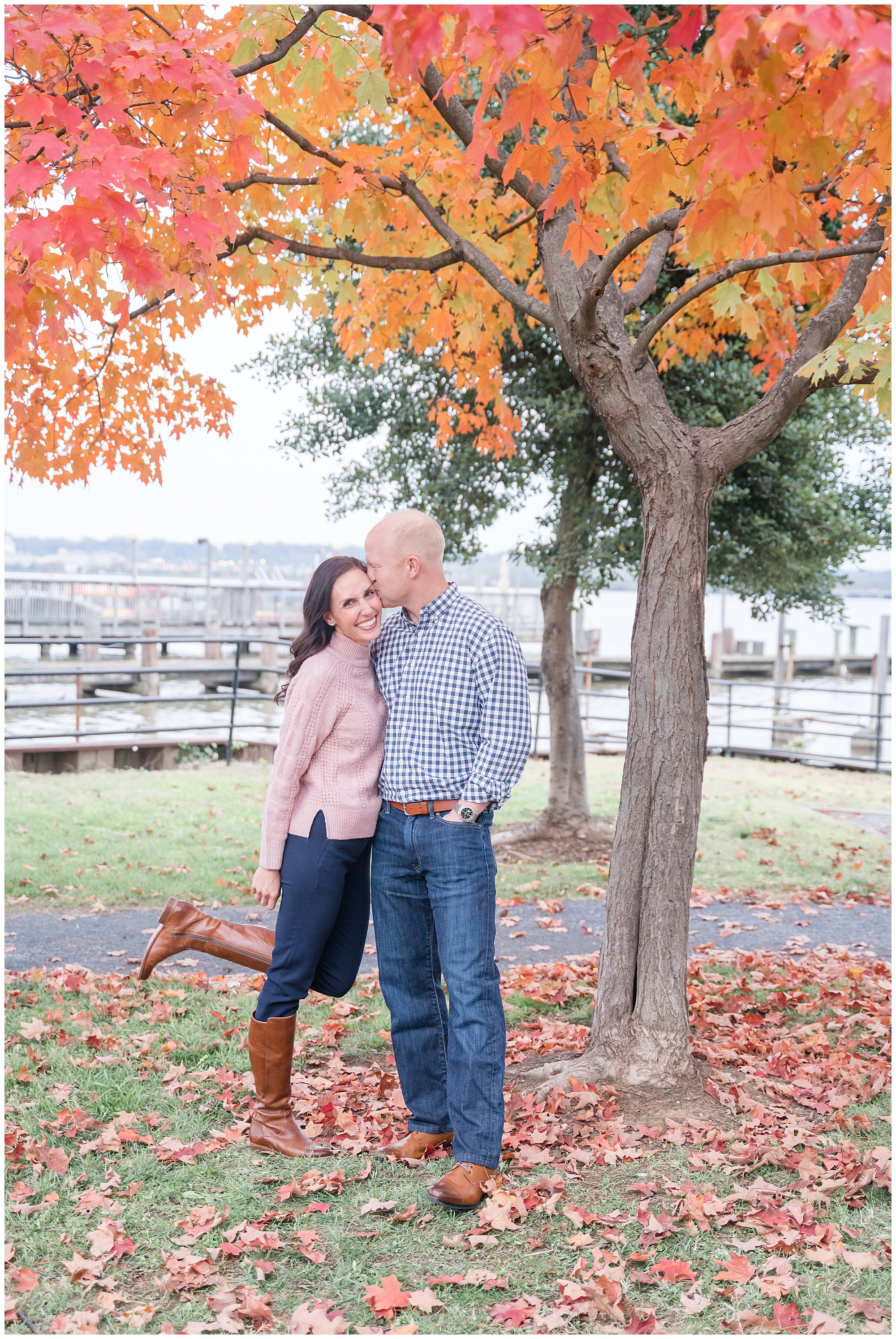 A husband kisses his wife on the cheek as she smiles at the camera while they're standing under a tree with bright red leaves during a fall photo session in Alexandria, Virginia.