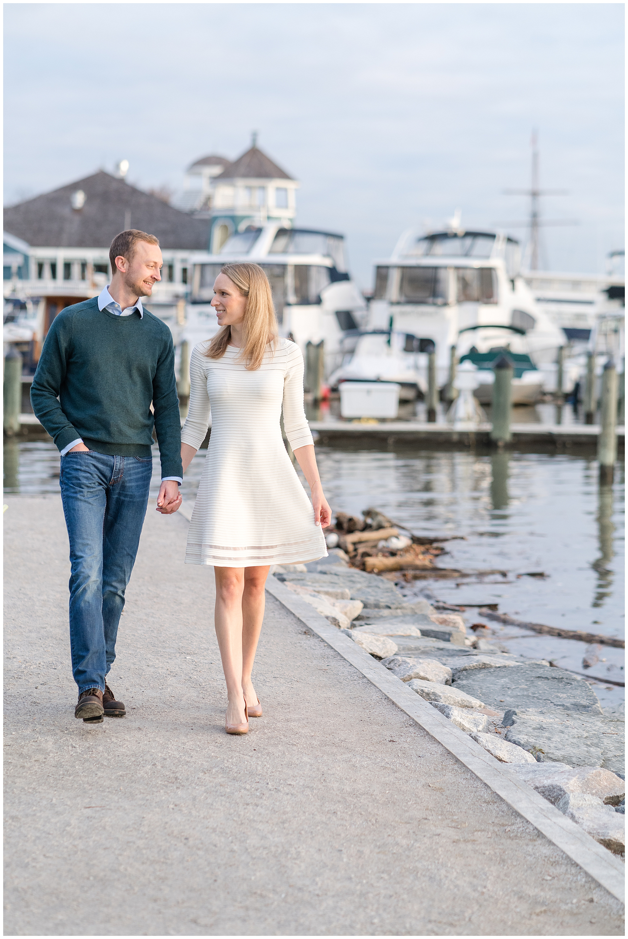 A couple walks by the water while holding hands during their Alexandria engagement session.