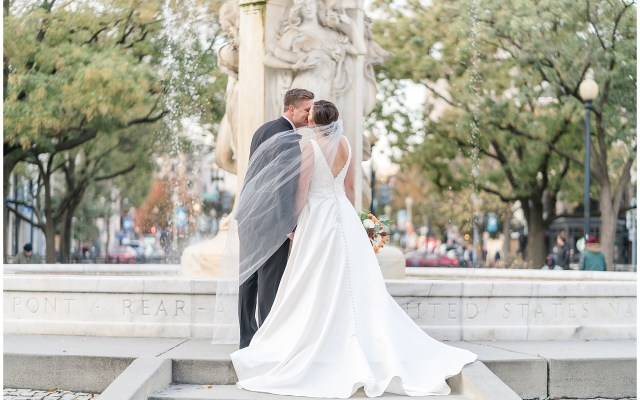 A bride and groom kiss as they face DuPont Circle during their Washington DC wedding.