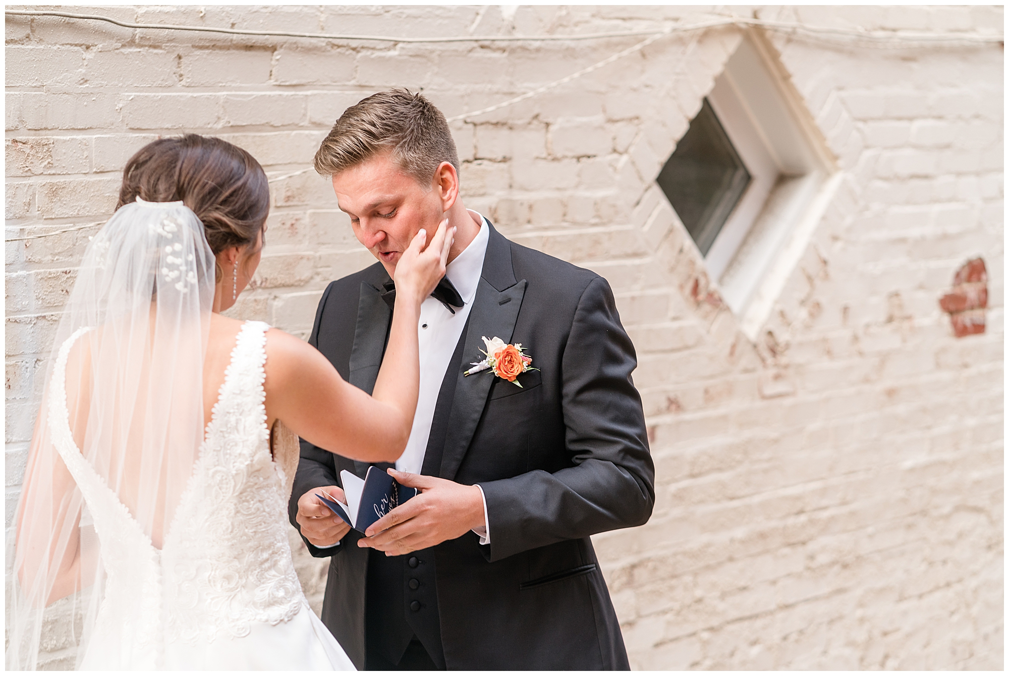 A bride touches her groom's cheek as he reads his vows during their Washington DC wedding.