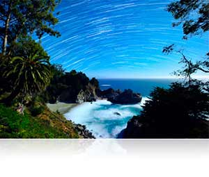 Time lapse photo of the stars in the night sky above a tropical island landscape in low light