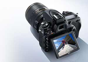 Photo of the D750 DSLR with NIKKOR lens and image of a parkour athlete on the LCD