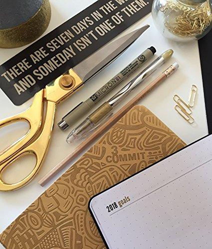 Commit30 Planner abierto a lado de algunos clips, tijeras, plumas y otros artículos de oficina. Se alcanza a ver un letrero con la frase