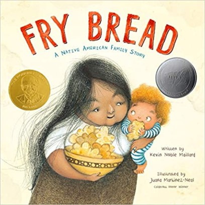image of a book cover for Fry Bread, a book that features Native American characters.  A Native American woman with long dark hair holding a red-haired baby in one arm and a bowl of bread in the other arm.