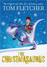 Front cover of Tom Fletcher's book, The Christmasaurus. It depicts a young boy riding on the back of a dinosaur surrounded by snowflakes.