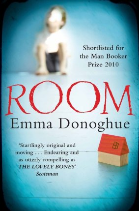 The book cover for Room by Emma Donoghue. A child sits at the far wall. Blurred. At the front is a toy house made from toy bricks.