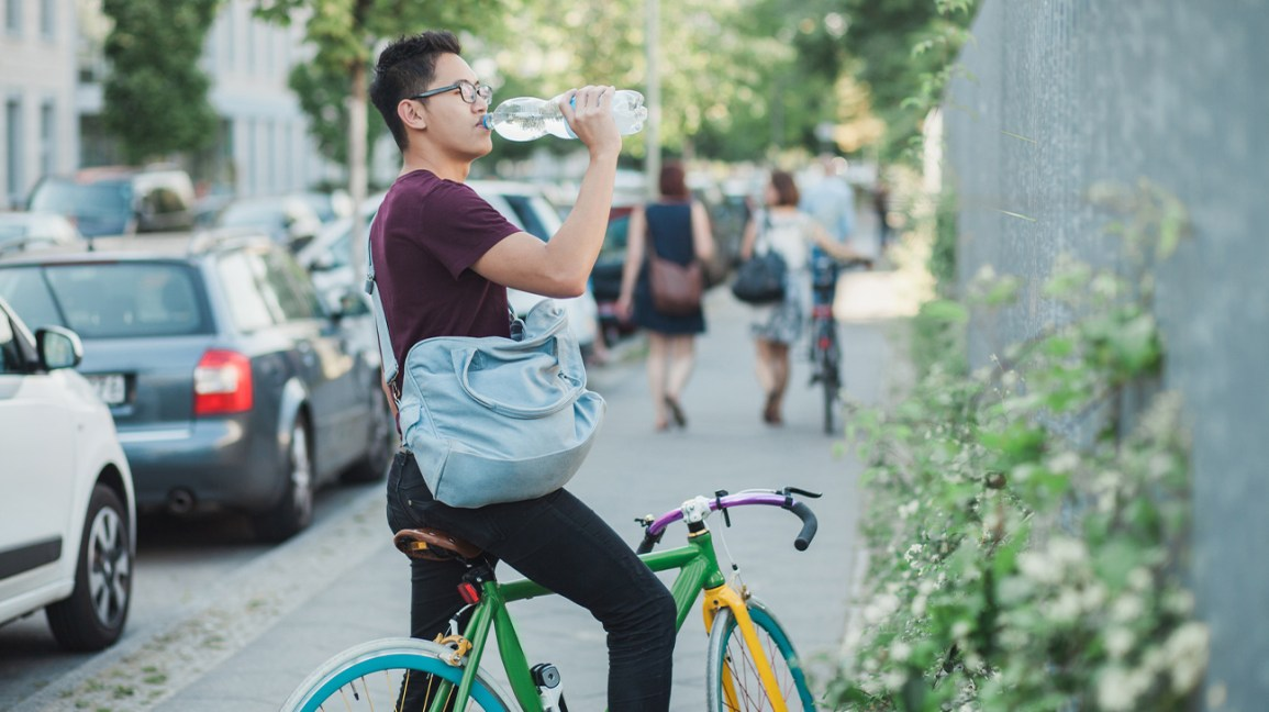 man on bike drinking from one-liter water bottle