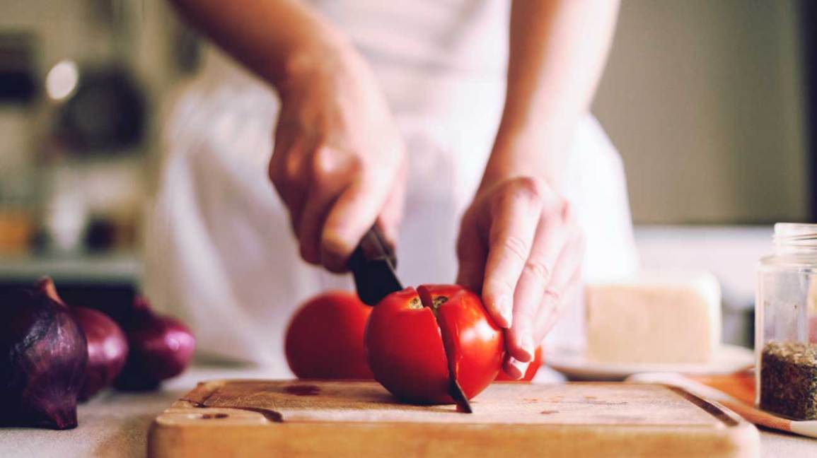hands cutting tomato on cutting board