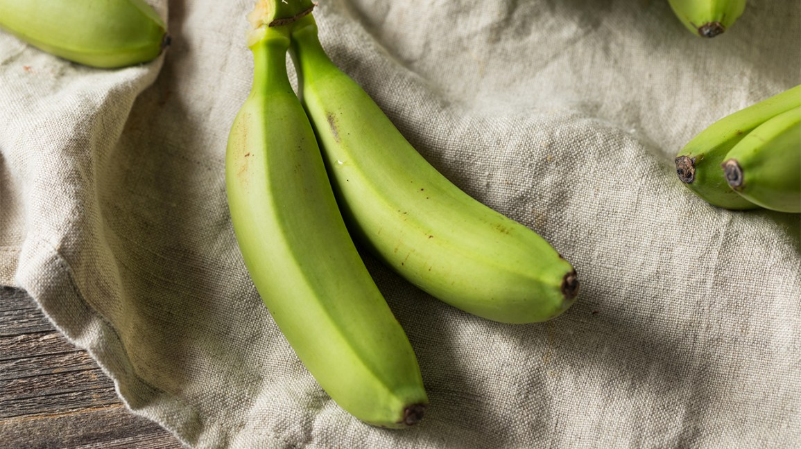 green, unripe bananas on a tablecloth