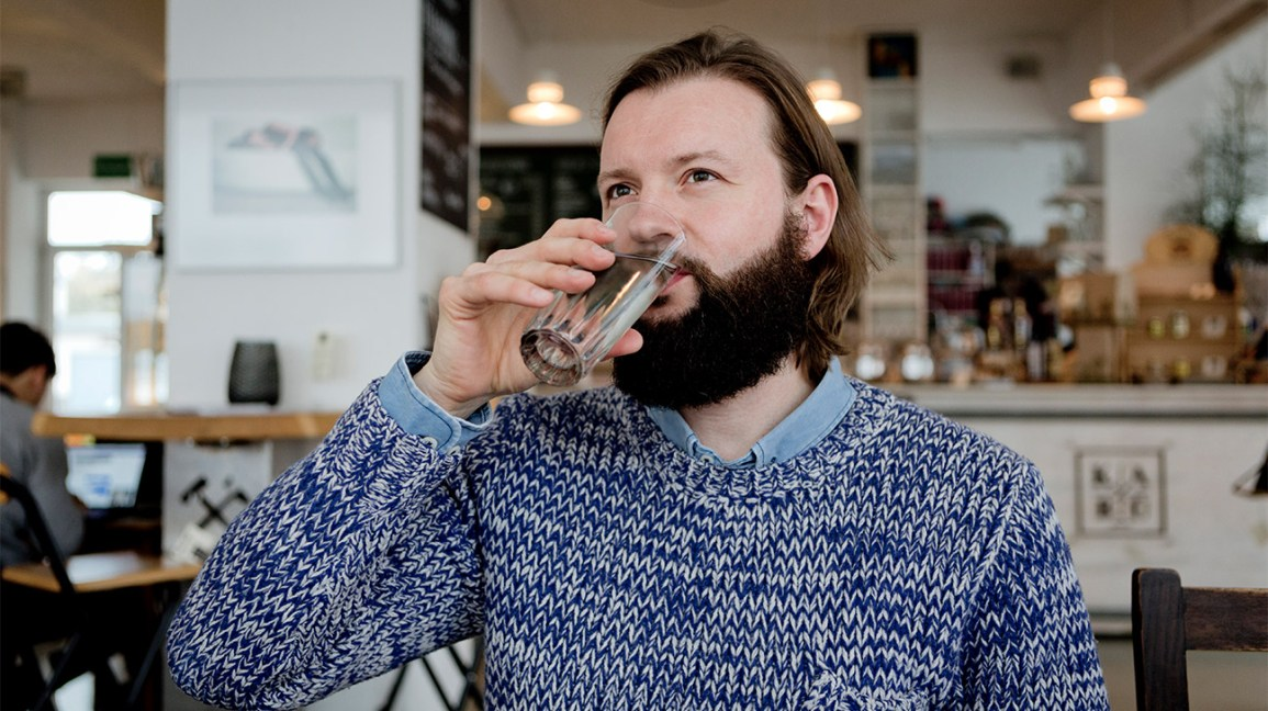 man drinking water at a cafe