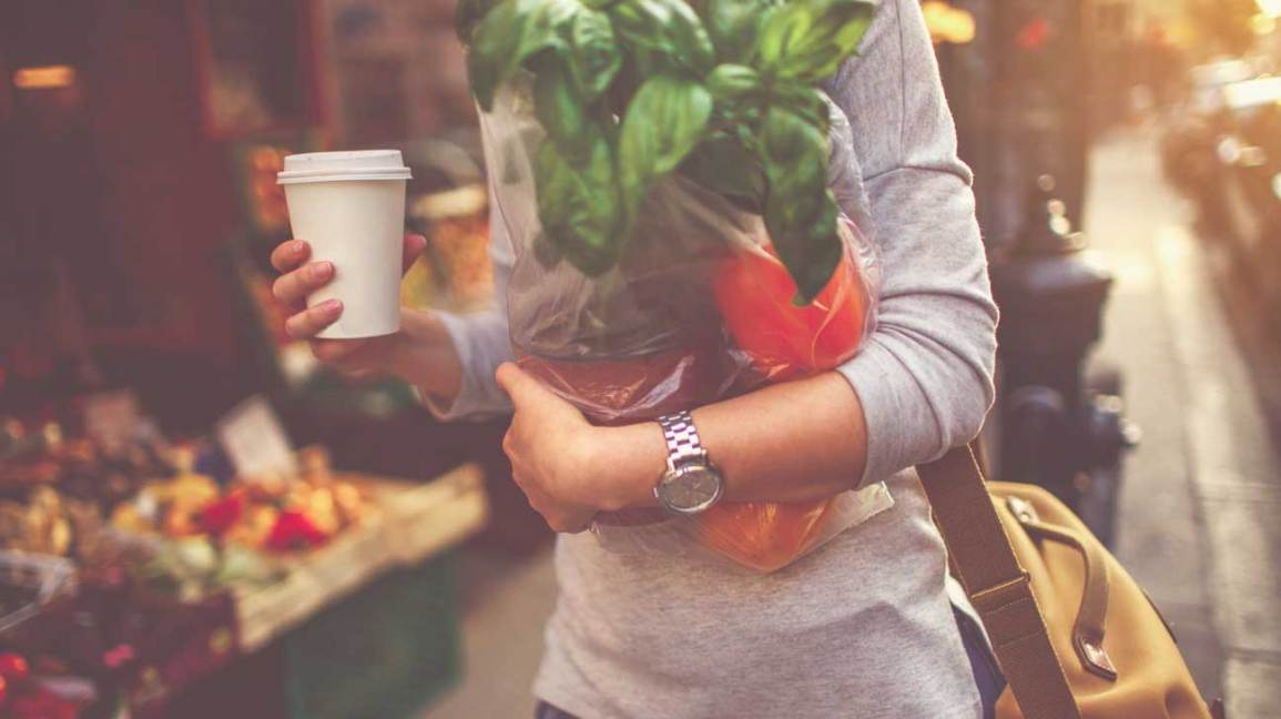 Woman Holding Coffee and Veggies