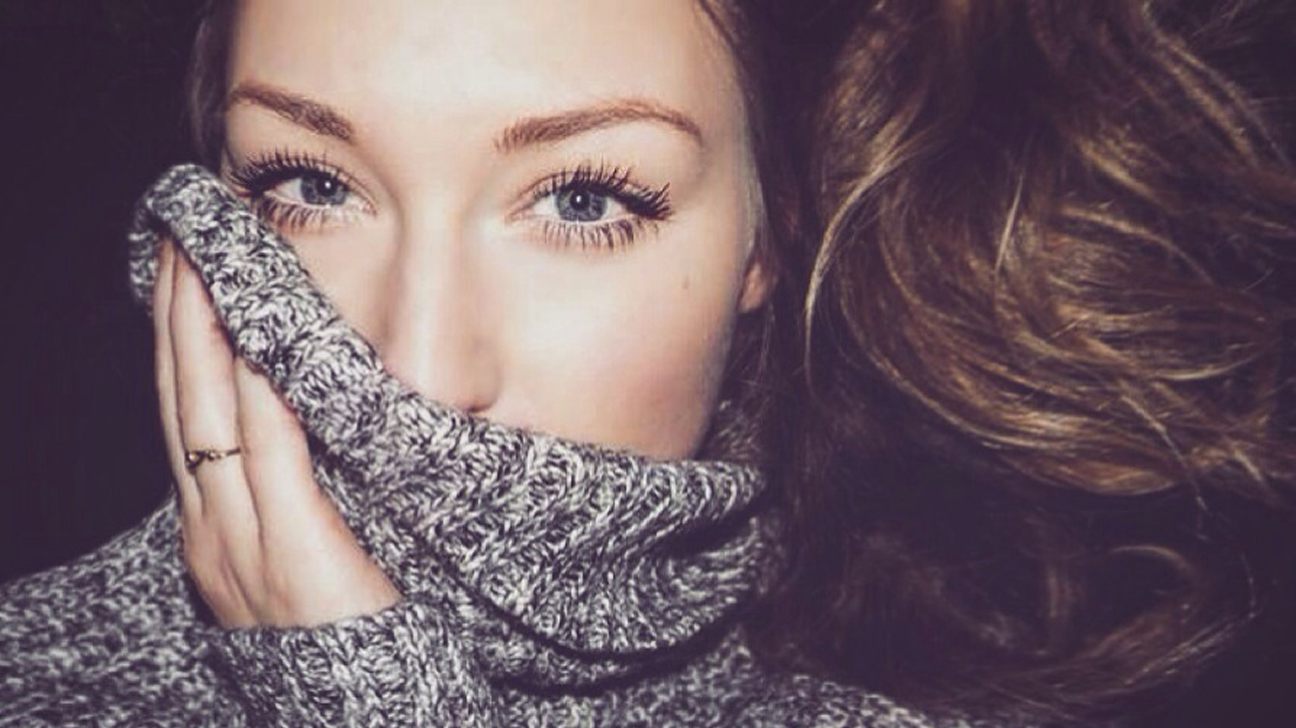 Young Woman Covering Mouth With Sweater
