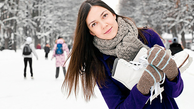 woman in snow holding ice skates
