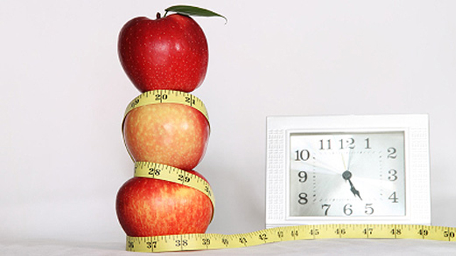 stacked apples wound in measuring tape