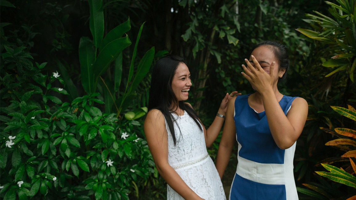 two embarrassed women laughing