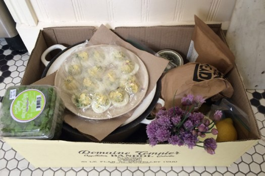 A box with a platter of deviled eggs, flowers, and salad greens.