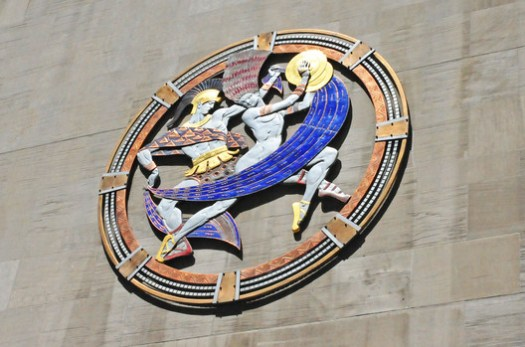 The Dancers' Medallion on the exterior of the Hall. Used under <a href='https://creativecommons.org/licenses/by-sa/2.0/'>Creative Commons</a>. ImageCourtesy of Flickr user Heather Paul