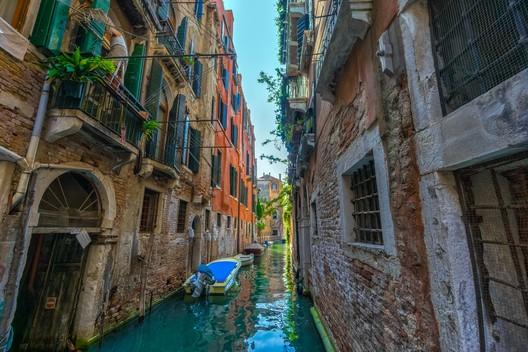 Image <a href='https://www.pexels.com/photo/white-boat-near-brown-concrete-building-227417/'>via Pexels</a>