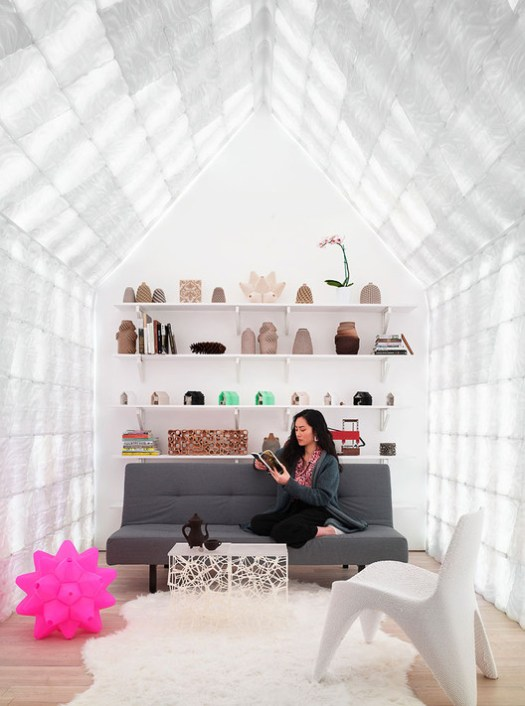 The interior displays 3D printed curiosities, from ceramic vessels, material experiments, and studies. Color changing LED lights, which illuminate the interior through the 3D-printed bio-plastic interior cladding, set a playful mood. 3D-printed furniture and accessories include a pink Picoroco Lamp, coffee table, Coffee-Coffee kettle and cup, and a chair. Image © Matthew Millman