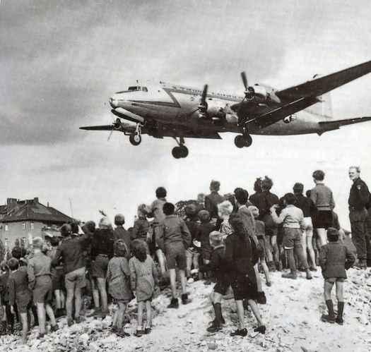 Children watch an American plane land with supplies at Tempelhof Airport during the Berlin Airlift. Image© <a href='https://commons.wikimedia.org/wiki/File:C-54landingattemplehof.jpg'>United States Air Force Historical Research Agency</a> licensed under <a href='https://creativecommons.org/licenses/by-sa/3.0/'>CC BY-SA 3.0</a>