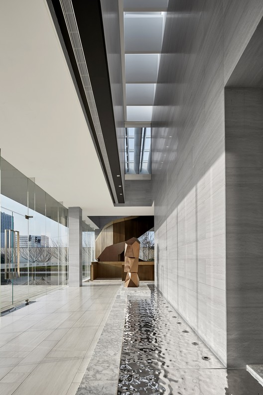 Light and shadow changing reception area stone wall. Image © Jianghe Zeng