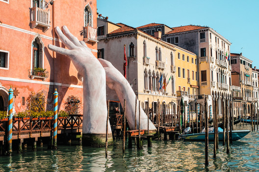 "Venice, Italy / February 17, 2018: sculpture ""Support"" for the Biennale 2017. Author - Lorenzo Quinn. . Image © Shutterstock/ by Evgeniya Telennaya"