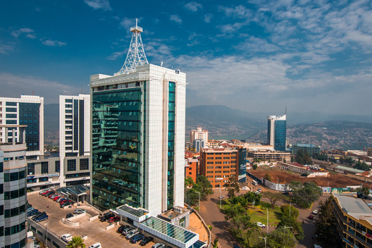 Kigali, Rwanda - September 21, 2018: a wide view looking down on the city centre with Pension Plaza in the foreground and Kigali City Tower in the background against a backdrop of distant blue hills. Image via Shutterstock/ By Jennifer Sophie