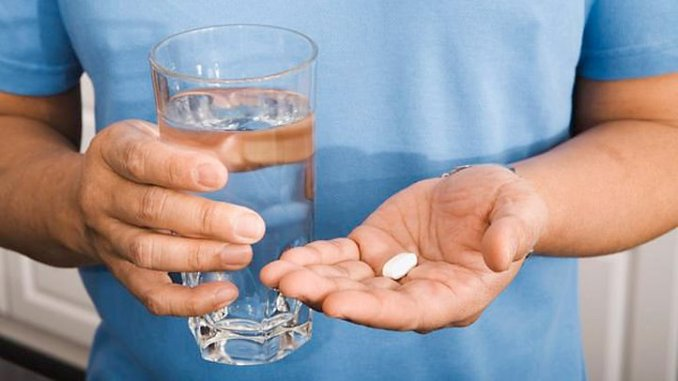 a man holding medication and a glass of water