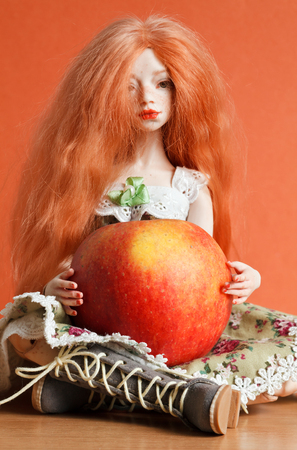 Beautiful Red Haired Doll And A Red Apple On An Orange Background
