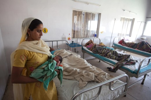 A woman holds a child in the post-delivery ward of the district hospital in Jind, Haryana, India. (Photographer: Prashanth Vishwanathan/Bloomberg)