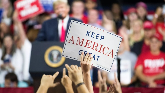 "Supporters at a Trump rally hold up a ""Keep America Great"" sign"
