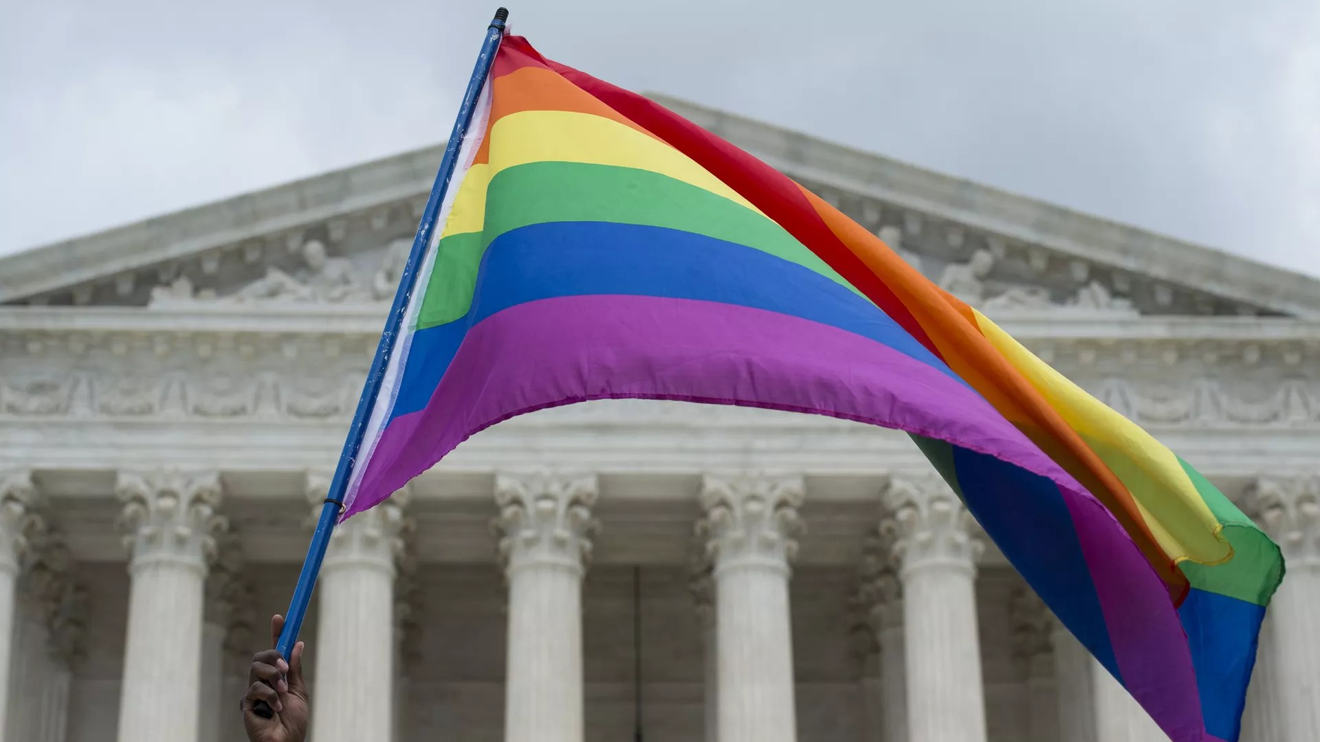 A rainbow flag flies in front of the U.S. Supreme Court.