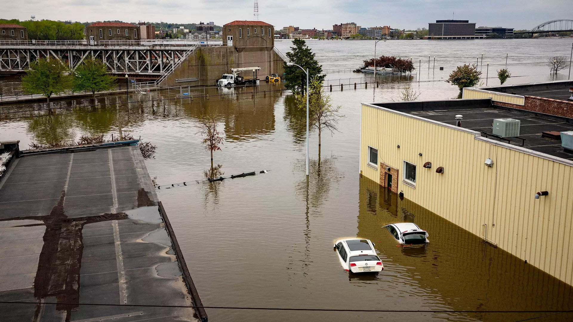 In this image, two cars float in the flood water between two buildings. This picture is a birds eye view of flood waters in a city.