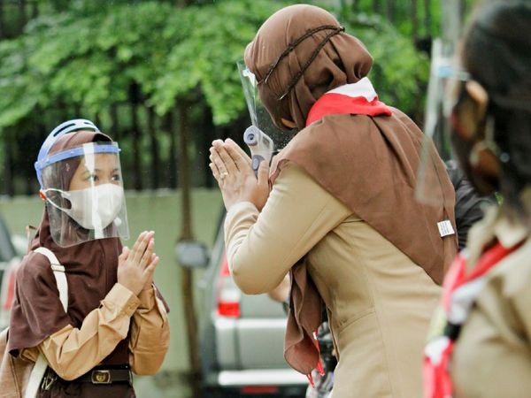 फोटो इंडोनेशिया के जकार्ता की है। यहां लंबे समय बाद फिर से स्कूल खुल गए। बचाव के लिए बच्चे फेस मास्क के साथ फेस शील्ड भी पहनकर स्कूल पहुंच रहे हैं।
