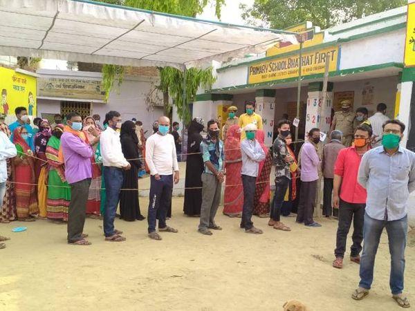 गोरखपुर के भटहट प्राथमिक विद्यालय में सोशल डिस्टेंसिंग का पालन करते हुए मतदाता।