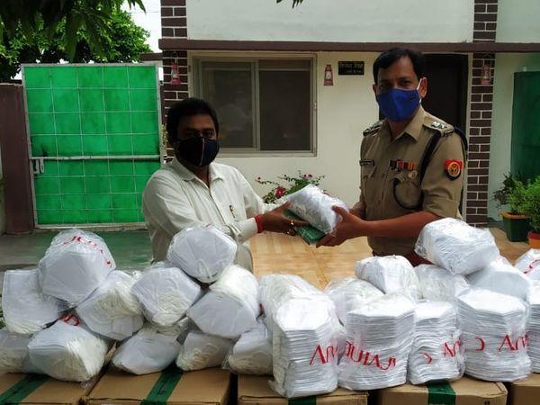 Police officers distributing masks sent by Smriti Irani.