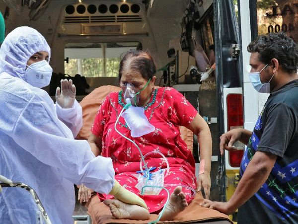 संक्रमण के बढ़ते मामले के बीच एक बुजुर्ग महिला को हॉस्पिटल में ले जाते BMC के स्वास्थ्यकर्मी।