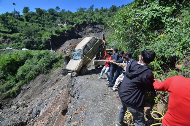 People try to pull over a car that fell after a landslide in Shimla.