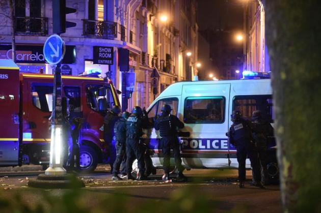 epa05024070 Police officers gather outside the Bataclan concert venue in Paris, France, 13 November 2015. At least 149 people have been killed in a series of attacks in Paris on 13 November, according to French officials. EPA/CHRISTOPHE PETIT TESSON