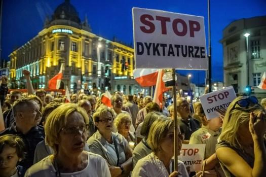 Hallituksen vastaiset mielenosoittajat kantavat käsissään kylttejä Puolassa.