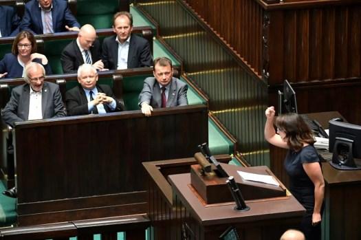 Miehiä tummissa puvuissa ja nainen mustassa mekossa puhujanpöntössä.